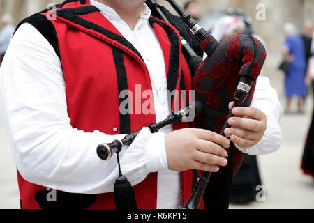 Detail of a man playing the Galician bagpipe, dressed in a traditional costume of Galicia, northwestern Spain - Stock Photo