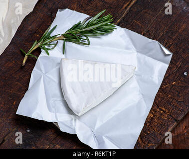 piece of brie cheese on paper - Stock Photo