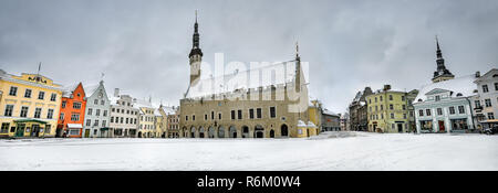 Panoramic landscape with Town Hall building and houses in Raekoja square at winter snowy day. Tallinn, Estonia - Stock Photo