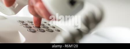 Wide view image of male hand holding white telephone handset dialing a phone number. Closeup view. - Stock Photo