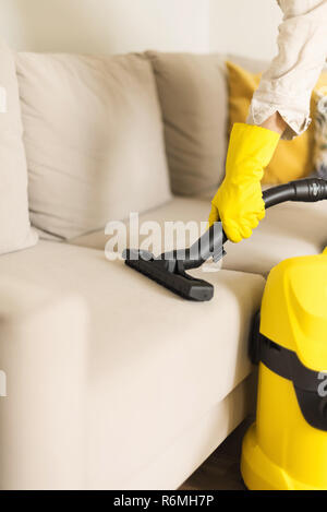 Woman cleaning sofa with yellow vacuum cleaner. Copy space. Clean concept. - Stock Photo