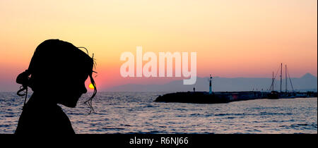 Silhouette of a young girl with sunset over the sea in Gouves, Crete, Greece - Stock Photo
