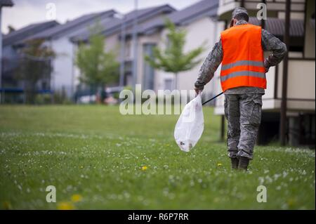 Airman Michael Agostino, 52nd Communications Squadron client systems technician, picks up trash during Spangdahlem's Eifel Pride base cleanup at Spangdahlem Air Base, Germany, May 18, 2017. The two-week program improves base appearance while also allowing Spangdahlem's first-term Airmen in-process and become familiar with their new duty station. - Stock Photo