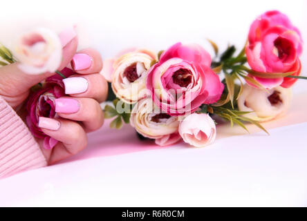 Nail design manicure decorated with flowers. Hands of woman with pink and white manicured on nails holding beautiful roses - Stock Photo