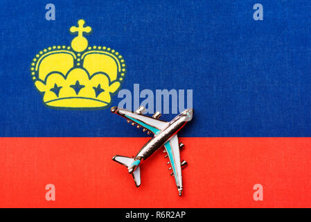 Airplane over the flag of Liechtenstein the concept of the journey. Toy plane, tourism and travel. - Stock Photo