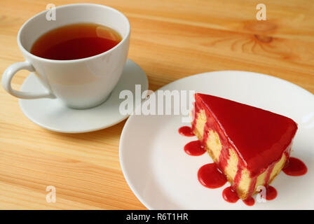 Plate of baked cheesecake with raspberry sauce with a cup of hot tea served on wooden table - Stock Photo