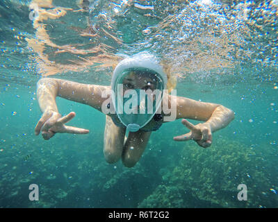 Young woman snorkeling in the ocean - Stock Photo