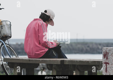 Female adult with kepi sits on wooden bench and reads a book at park along seashore, beside her bicycle, Hualien, Taiwan. Vintage toned - Stock Photo