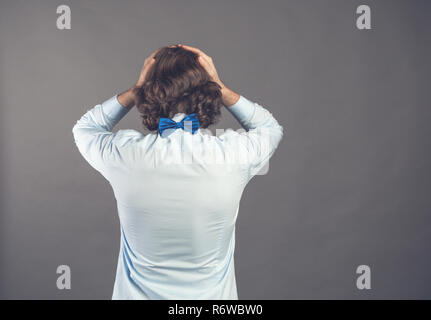 Backside view standing young man with shaggy curly hair wearing blue shirt and bow tie against grey background. Holding head, depression. Negative despair emotion concept. Rear view people collection. - Stock Photo