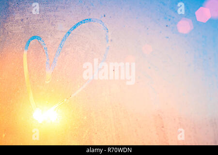 Heart on winter glass with sunbeams. Heart painted on the frozen winter window - Stock Photo