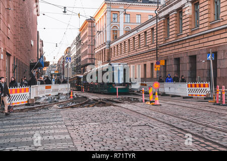 Editorial 11.17.2018 Helsinki Finland, urban view with tram and people walking despite some road work - Stock Photo