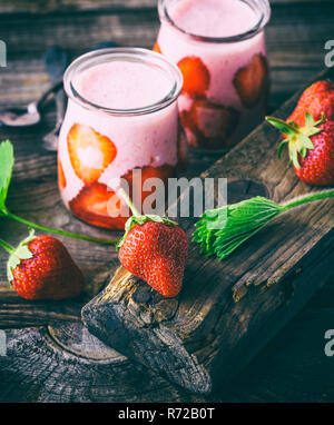 red strawberry and two glass jars of smoothies - Stock Photo
