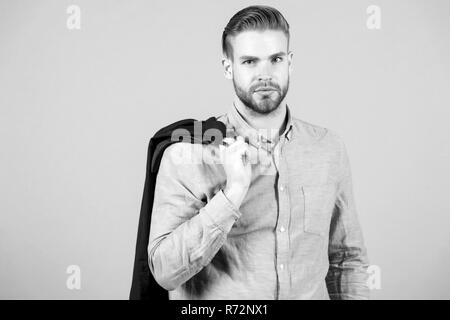 Macho in blue shirt pose with jacket on shoulder on grey background. Fashion, casual style concept - Stock Photo