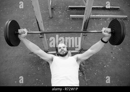 Weightlifting, bodybuilding, fitness, sport. Bodybuilder lift barbell on stadium. Man with athletic torso, strong arms training with weight. Power, energy, strength concept - Stock Photo