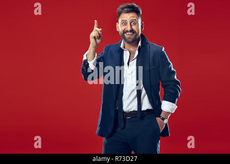 The young attractive man looking suprised isolated on red - Stock Photo