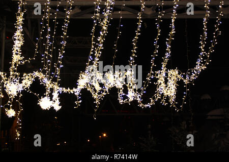Christmas garland on the street with traffic lights on the background - Stock Photo