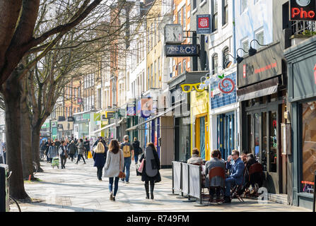 London, England, UK - March 27, 2017: Pedestrians and shoppers walk past traditional high street shops on Upper Street in Islington Angel, North Londo - Stock Photo