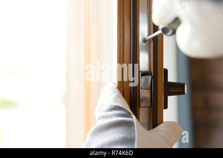 Construction worker installing window in house. Handyman fixing the window with screwdriver - Stock Photo