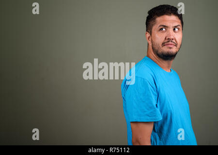 Bearded Persian man wearing blue shirt against colored backgroun - Stock Photo