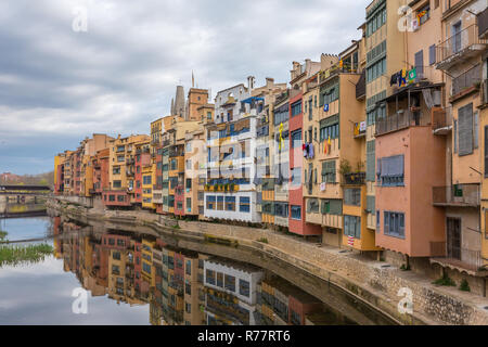 Colorful yellow, red and orange houses with the Catalan flags reflected in water river Onyar, in Girona, Catalonia, Spain. - Stock Photo
