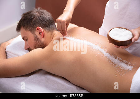 Close-up Of Therapist Hand Applying Salt On Young Man's Back - Stock Photo