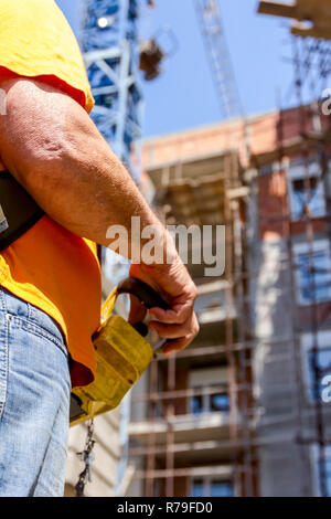 Operator, worker is holding industrial remote, wireless, console to control overhead crane with joystick at construction site. - Stock Photo