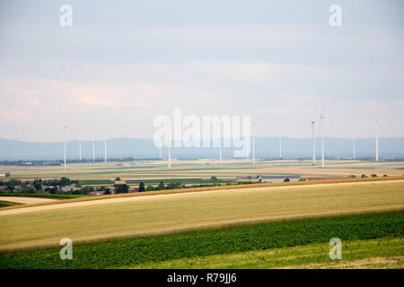 flat farmland landscape with wind wheels and houses in background with cloudy sky in early summer at day - Stock Photo