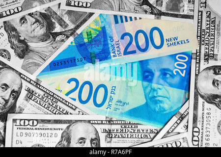 Two new bills of 200 shekels are on the background of 100 dollar. Cash background of black and white dollar bills, top view. - Stock Photo