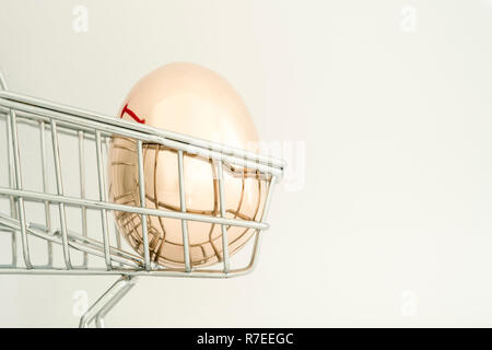 A Golden egg made of metal in a supermarket grocery cart on a light gray background. The concept of a unique offer for the client. Copy space. - Stock Photo