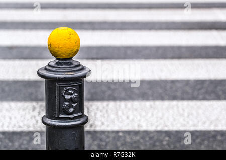 yellow metal ball on parking pole, below Warsaw coat of arms, blurred pedestrian crossing in background - Stock Photo