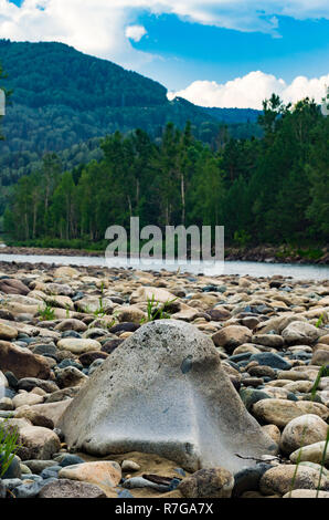 Big boulder on a river bank in the forest with mountains in background on a summer morning - Stock Photo