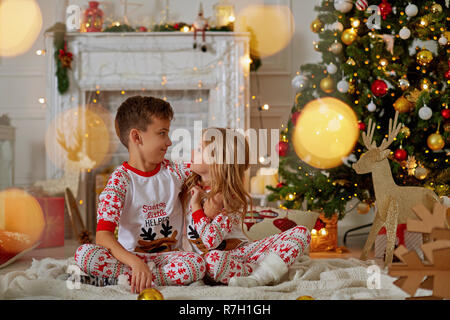 Happy little kids in matching red and green striped pajamas decorate Christmas tree in beautiful living room with traditional fire place. Children opening presents on Xmas eve. - Stock Photo