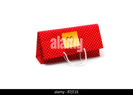 Gift bag with heart shape message, written by hand. Red polka dot paper bag isolated on white background. - Stock Photo