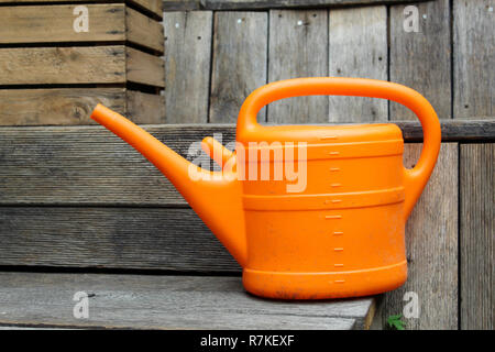 Orange watering can on wooden benches - Stock Photo