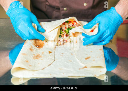 Cook prepares a shawarma. Ingredients in lavash - Stock Photo