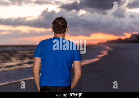 Florida dark red and orange sunset in gulf of Mexico with back of young man in blue shirt standing watching landscape - Stock Photo