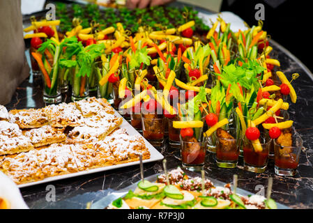 canapes and cold appetizers on the buffet table, meat, vegetables and herbs on a tray - Stock Photo