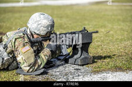 U.S. Army Pfc. Julius Forde zeroes his weapon before shooting a weapon qualification during the New York Army National Guard Best Warrior Competition at Camp Smith Training Site March 30, 2017. The Best Warrior competitors represent each of New York's brigades after winning competitions at the company, battalion, and brigade levels. - Stock Photo
