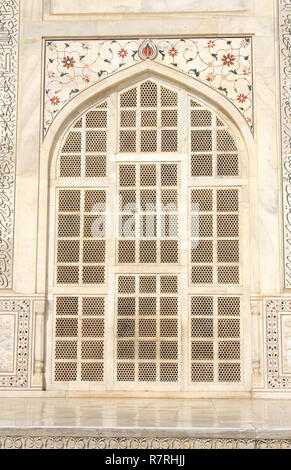 Carved window and mosaic on marble in Taj Mahal, India - Stock Photo