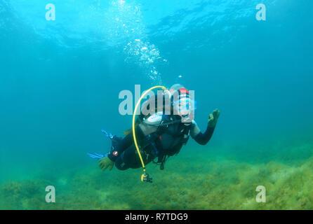 Woman scuba diving, making OK gesture, Black Sea, Crimea, Ukraine - Stock Photo