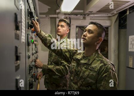 Spc. Huy Dinh and Spc. Dylan Nice, U.S. Army Reserve watercraft operator and engineer Soldiers from the 949th Transportation Company, a unit which specializes in watercraft operations, cargo and watercraft engineering, pose in the engine control room of a Logistics Support Vessel in Baltimore, Md., on April 7-8, 2017. - Stock Photo
