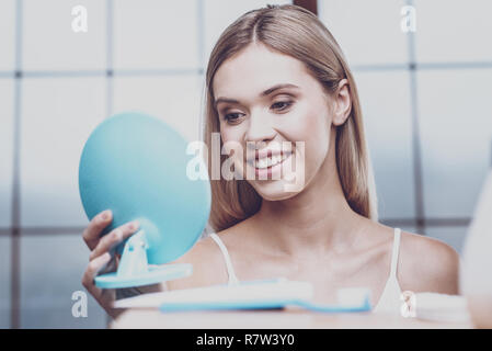 Young woman admiring her reflection - Stock Photo