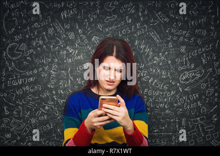 Confused young woman in front of a blackboard looking at her smartphone with puzzled face emotion trying to solve hard mathematics calculation, formul - Stock Photo