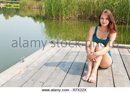 Portrait of a young woman sitting on a pier at the pond. Summer sunny day. She is wearing a sports jersey gymnastics. - Stock Photo