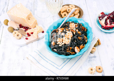Italian Pasta is black with mussels and shrimps. Parmesan, Seafood and wine for dinner. Bright dishes and white background - Stock Photo