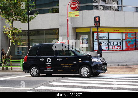 A Toyota JPN Taxi with Tokyo Olympic 2020 logo passes a Naito Securities branch with Japanese stock prices displayed in its window in Kayabacho, Tokyo - Stock Photo