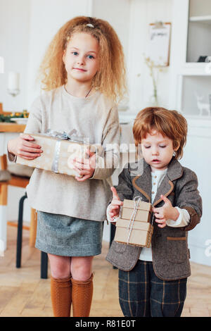 Little brother and the sister give gifts, toned photo - Stock Photo