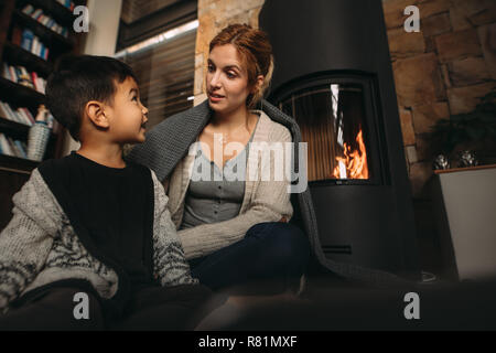 Woman wrapped in blanket sitting on floor with little boy in living room. Young mother and her little son by a fireplace at home. - Stock Photo