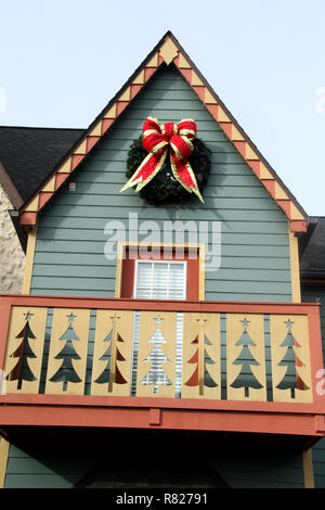 Red bow on Christmas wreath used as exterior decoration - Stock Photo