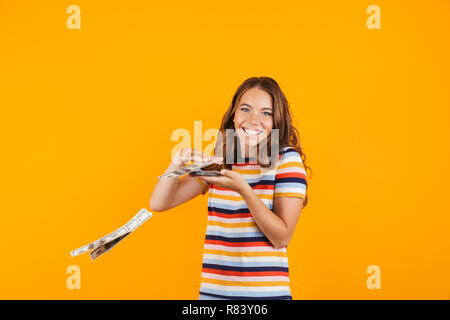 Portrait of a smiling cheerful young girl standing isolated over yellow background, throwing away money banknotes - Stock Photo